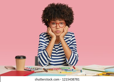 Sad dejected female architect feels unhappy as has no inspiration for creating masterpiece, sits at desktop, surrounded with crayons, notebook and disposable cup of coffee, holds chin isolated on pink