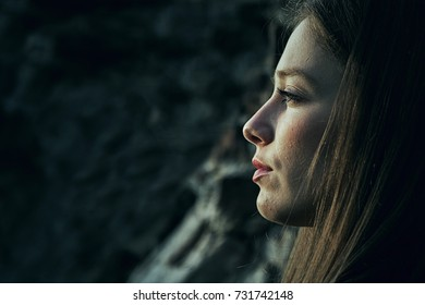 A sad and depressed alone outdoors. Outdoor portrait of a sad teenage girl. Lonely woman in despair