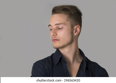 Sad, depressed blond young man looking down. Light grey background