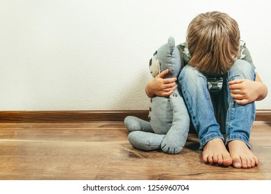 Sad depressed boy with teddy bear, time out discipline tactic, punishment
