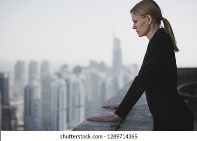 Sad and depressed business woman overlooking the city.