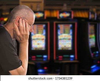 Sad and depressed caucasian man sitting with his hands on his head in front of rows of casino slot machines. Gambling addiction theme image.  Close up portrait.