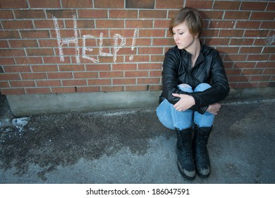 Sad, depressed girl outside school, with red brick background