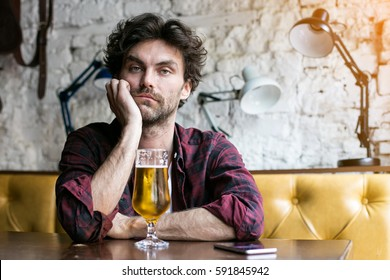 sad and depressed guy  having a beer in a pub, sitting alone at a table