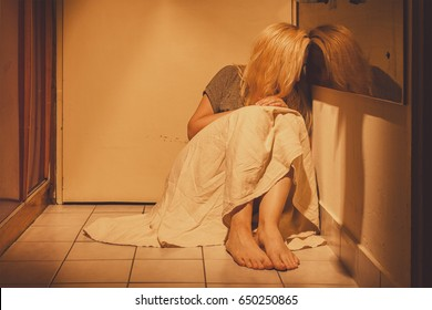 Sad, depressed and lonely woman sitting in a corner on a floor tiles, in a skirt, barefoot with a long blond hair