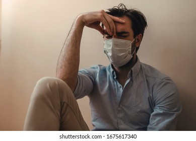Sad, depressed man during the coronavirus quarantine staying at home, going mental and crazy. Covid-19 home isolation
