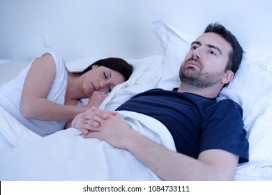 Sad and depressed man lying in the bed with his wife