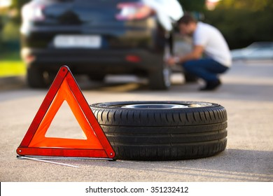 Sad and depressed man sitting near car with punctured tire