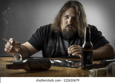 sad depressed man at a table with alcohol bottles, cigarettes and what looks like cocaine