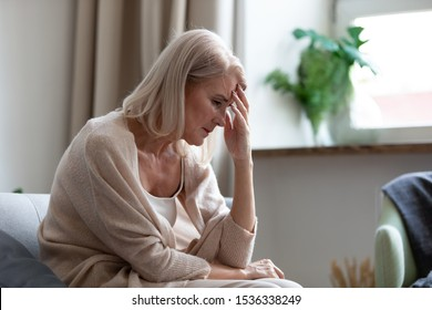 Sad depressed middle aged mature woman sitting alone at home touching head feeling headache migraine, upset tired old senior lady widow mourning suffer from grief loneliness mental problems concept