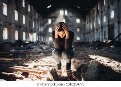 Sad depressed person in abandoned destroyed building crying.Emotional portrait.Woman lost everything.Desperate female.Stressed and overworked.Disappointment.Relationship problems.Anxiety concept.Ruins