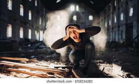 Sad depressed person in abandoned destroyed building crying.Emotional portrait.Screaming woman in excruciating pain.Problem,stress and disappointment.Disaster in life,lost and grief.Madness and trauma