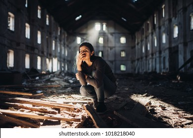 Sad depressed person in abandoned destroyed building crying.Emotional portrait.Problem,stress and disappointment.Disaster in life,lost and grief.Madness and trauma.Moarning