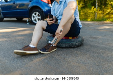 Sad and depressed person sits on a spare wheel near a blue car with a punctured tire and an open trunk. A man calls using a smartphone mobile tire service.