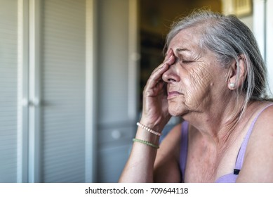 Sad depressed, stressed, thoughtful, senior, old woman, gloomy, worried, covering her face. Senior woman portrait. Saddened and afraid older woman is touching face