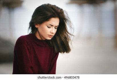 Sad Depressed Teen Girl Sitting alone on the Beach