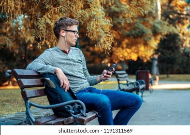 Sad, depressed teenager listening on music on park bench , introvert boy