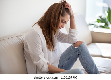 Sad depressed thoughtful young woman feeling bad at home, upset millennial lonely girl thinking of sorrow, regrets of mistake or worries about having psychological problem sitting alone on sofa