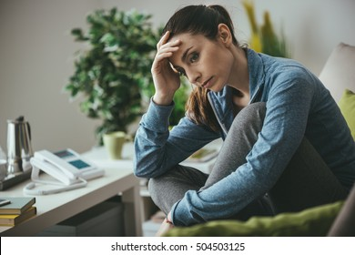 Sad depressed woman at home sitting on the couch, looking down and touching her forehead, loneliness and pain concept