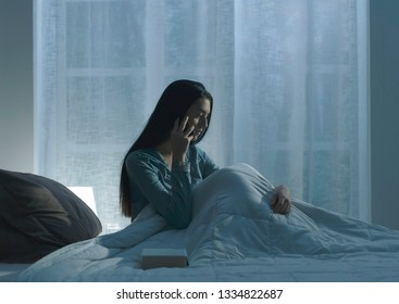 Sad depressed woman lying in bed late at night, she is suffering from insomnia and feels exhausted