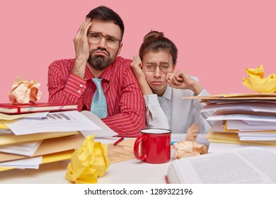Sad depressed woman and man coworkers look with displeasure, frown faces, being in despair as have deadline for exam preparation, stack of documentations near, sit in coworking space. Negative feeling