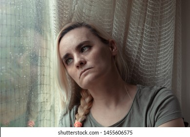 Sad, depressed woman sitting by the window, looking longingly out and daydreaming
