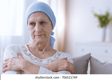 Sad depressed woman suffering from malignant breast cancer sitting alone