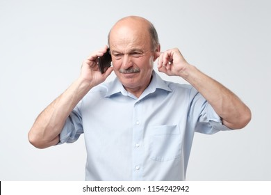 Sad, depressed, worried senior man, father talking on phone, isolated white background. Bad connection. He can not hear what he is told.
