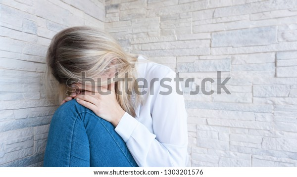 Sad or Depressed Young Beautiful Woman at home on brick wall background