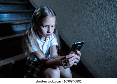 Sad depressed young girl victim of cyberbullying by mobile smart phone sitting on stairs feeling lonely, unhappy, hopeless and abused. Bullied by text message. Dark light