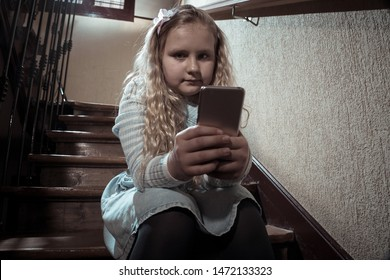 Sad depressed young girl victim of cyberbullying by mobile smart phone sitting on stairs feeling lonely, unhappy, hopeless and abused. Child bullied and harassed by text message by online stalker.