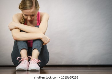 Sad depressed young teenage girl sitting by wall hiding face. School, adolescence, home violence, unwanted love problems.