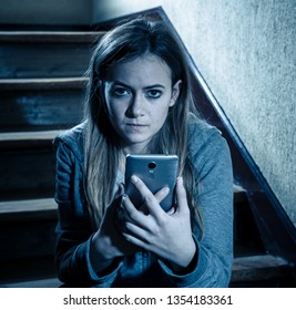 Sad depressed young teenager girl victim of cyberbullying by mobile smart phone siting on stairs feeling lonely, unhappy, hopeless and abused. Bullied by text message on social media app. Dark light