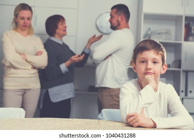 Sad desperate little boy during parents quarrel in home interior