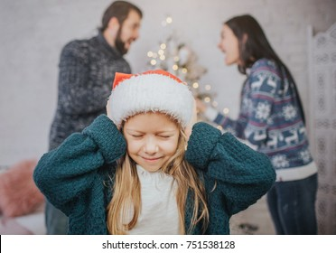 Sad, desperate little girl during parents quarrel. Clog the ears.. Family quarrel on the eve of Christmas