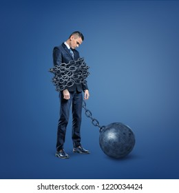A sad disappointed businessman stands bound by a wide metal chain which is locked to an iron ball. Ball and chain. Restriction and prison. Bound by laws.