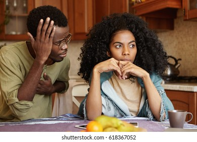 Sad disappointed woman can't forgive her husband for infidelity who is sitting next to her having apologetic guilty look, saying it was a mistake. African American couple facing relationships problems