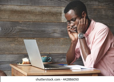 Sad and disappointed young black freelancer in glasses and pink shirt sitting at the table at a cafe, checking voicemail on mobile phone and finding out that the investor cancelled the meeting