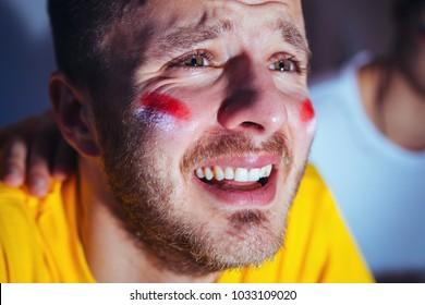 Sad, disappointing football fan crying, closeup