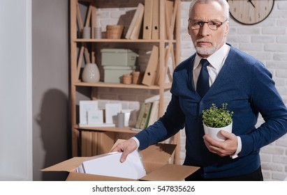 Sad dismissed office worker putting away his things