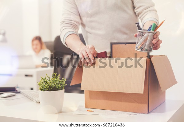 Sad dismissed worker taking his office supplies with him