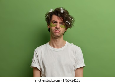 Sad dissatisfied young man cares about skin and beauty, looks in discontent at camera, wears collagen patches under eyes, has bad mood as awakes very early, prepares for date, poses at home.