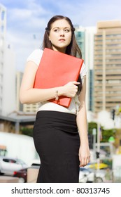 Sad Distressed And Devastated Young Business Woman Crying And Sobbing While Walking With Red Folder In Hand In A Sad And Unhappy Business Concept