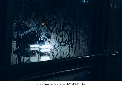 A sad drawing on the sweaty glass of a child's bear with hearts against the light of headlights