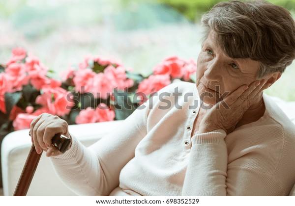 悲しい老婦人がソファに座り、体調を気にしている