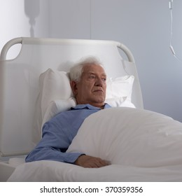 Sad elder man lying in hospital bed