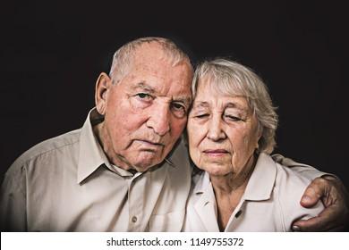 Sad elderly couple on a the black background