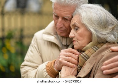 Sad elderly couple standing embracing outdoors