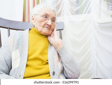 Sad elderly lady sitting in a chair and thinking.