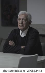 Sad elderly lonely man sitting at home